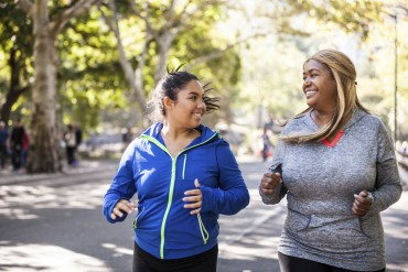 Two plus size women jogging in Central Park, New York during a beautiful day.