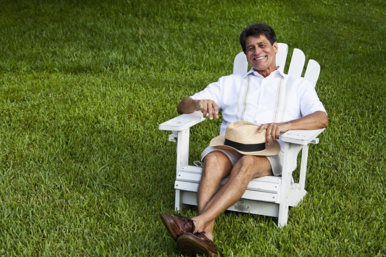 Mature man (Hispanic/Native American, 50s) sitting in adirondack chair, laughing.
