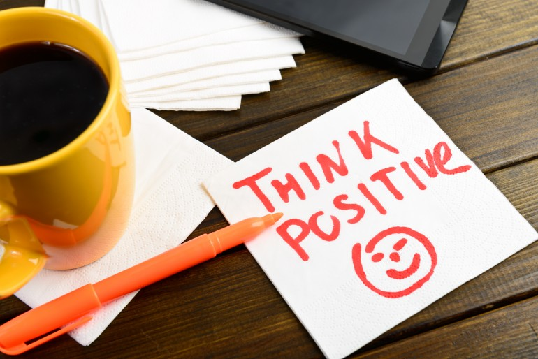 Think positive writing on white napkin
