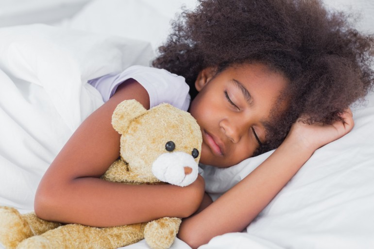 Cute little girl sleeping in bed cuddling teddy bear at home in bedroom