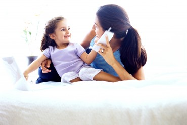 shot of a young woman sitting on a bed with her daughter and talking on the phone