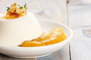 A dessert of vanilla Panna Cotta with lemon and fresh herbs